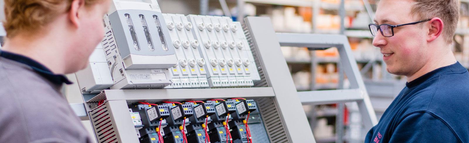 Zwei Mitarbeiter der ROBIN GmbH an einer elektrischen Anlage